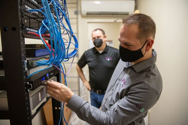 Technician looking over a network switch
